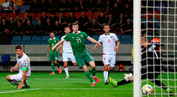 Paddy power: Midfielder Paddy McNair fires home the late winner in Borisov to keep Northern Ireland's perfect start to Group C intact