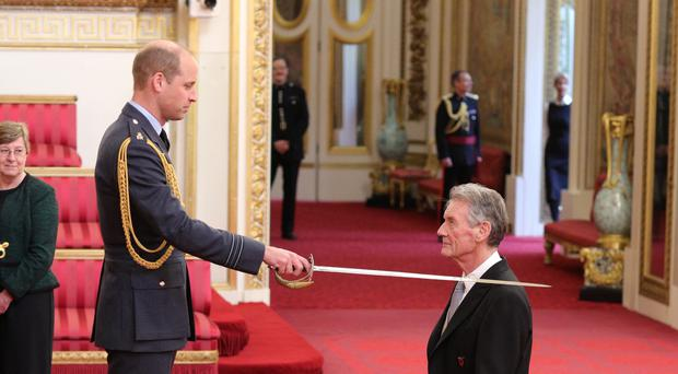 Sir Michael Palin is made a Knight Commander of the Order of St Michael and St George by the Duke of Cambridge (Yui Mok/PA)