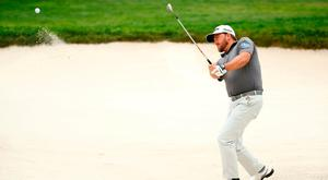 Rescue mission: Graeme McDowell practices his bunker shots yesterday