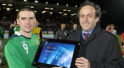 On duty: Then Uefa president Michel Platini presents NI striker David Healy with a special award for his heroics in scoring a record 13 goals during the Euro 2008 qualifiers