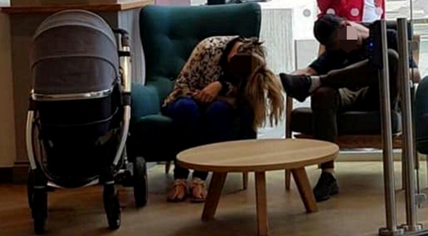 The couple pictured slumped in their chairs next to the baby's pram in a Belfast building
