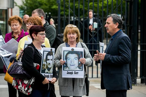 Families of the people who were killed during a disputed series of shootings in the Ballymurphy area of Belfast in August 1971 hold images of their loved ones with supporters outside Belfast Laganside Courts, during a new inquest into their loved ones deaths. Photo credit: Liam McBurney/PA Wire