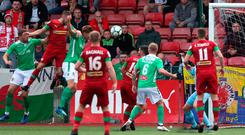 Head man: Conor McMenamin leaps highest to open the scoring for Cliftonville