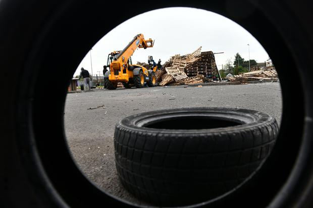 Bonfire builders at the Avoniel Leisure Centre site voluntarily remove tyres from their bonfire this afternoon after a ruling from the City Council. Credit: Pacemaker