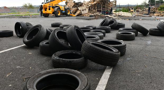 Bonfire builders at the Avoniel Leisure Centre site voluntarily remove tyres from their bonfire after a ruling from the City Council. Credit: Pacemaker