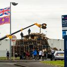 A crowd gathers to watch men remove material from a July 11th night bonfire at Avoniel Leisure Centre. Pic: PA Wire