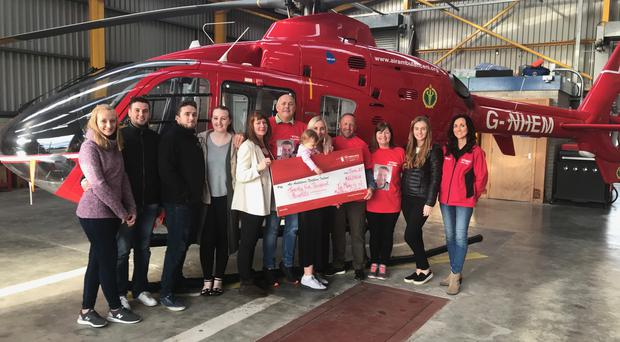 Presenting the cheque to Kerry Anderson, head of fundraising for AANI are Rachael Newberry, Ross McKaig, Mark Magill, Judy Newberry, Pamela Campbell, Mark Campbell, Ashley Boyd with Zara Boyd, Darren Newberry, Karen Newberry and Matthew's fiancee Robyn Newberry