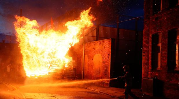 Members of the fire service work to contain an 11th night Bonfire in Cluan Place, Belfast. Credit: Brian Lawless/PA Wire