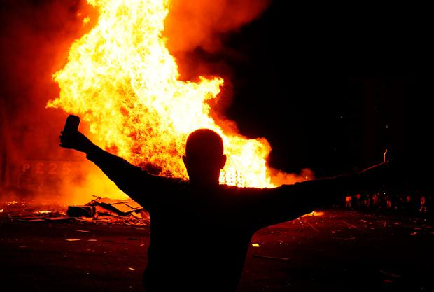 People attend an 11th night Bonfire in the Sandy Row area of Belfast. Photo credit: Brian Lawless/PA Wire