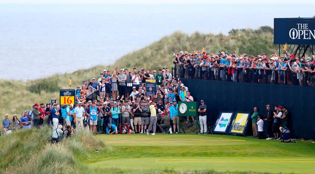 Crowds watch Tiger Woods tee off on the 16th during his second practice round at Royal Portrush.