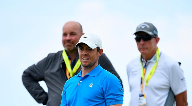 Looking on: Rory McIlroy is watched by former Ryder Cup captain Thomas Bjorn and coach David Leadbetter at Portrush