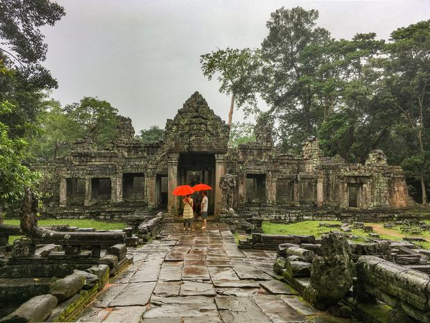 Angkor Wat, Siem Reap, Cambodia, August 2018. Toursts with red umbrellas in the rain at the ruins of ancient Khmer temple.