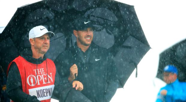 Brooks Koepka shelters under an umbrella with caddie Ricky Elliot during the first round of the Open Championship at Royal Portrush (Andrew Redington/Getty Images)