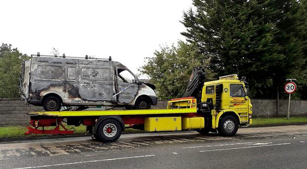 A burnt out van being removed from the scene. Photo By Justin Kernoghan