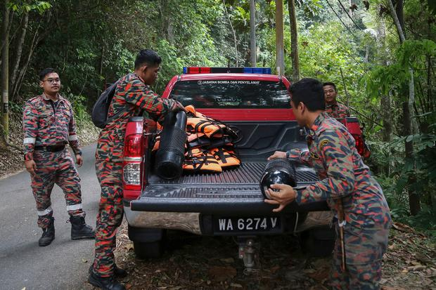 Members of rescue team prepare oxygen tanks as they prepare to conduct a search and rescue operation for a missing British girl in Seremban, Malaysia (AP Photo/Annice Lyn)