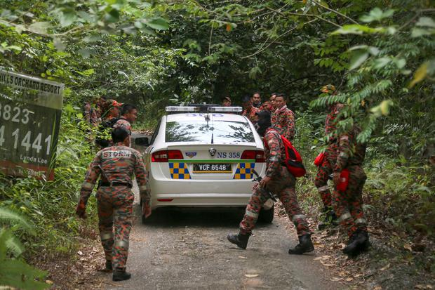 Members of rescue team enter a forest to conduct a search and rescue operation for a missing British girl in Seremban, Malaysia (AP Photo/Annice Lyn)