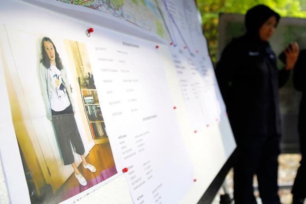 A police officer stands near a photo of missing British girl Nora Anne Quoirin in Seremban, Negeri Sembilan, Malaysia, Thursday, Aug. 8, 2019. Malaysian police said Wednesday they were analyzing fingerprints found in a forest resort cottage where the British teenager was reported missing and did not rule out a possible criminal element. (AP Photo/Lai Seng Sin)