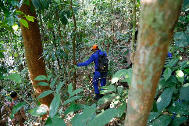 A member of a rescue team conducts a search and rescue operation for a missing British girl at a forest in Seremban, Negeri Sembilan, Malaysia, Thursday, Aug. 8, 2019. Malaysian police said Wednesday they were analyzing fingerprints found in a forest resort cottage where Nora Anne Quoirin, the British teenager missing in Malaysia, was reported missing and did not rule out a possible criminal element. (AP Photo/Lai Seng Sin)