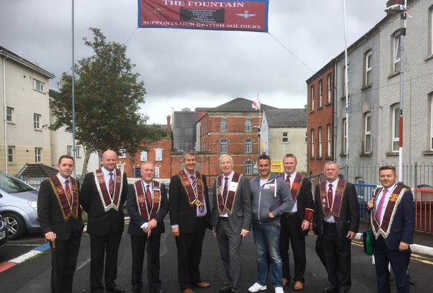 DUP representatives including MP Gregory Campbell and MLAs Gary Middleton and Edwin Poots pose under a banner in Londonderry's Fountain Estate on Saturday.