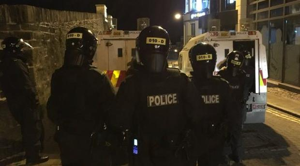 Police officers in riot gear in Londonderry on Monday night. Credit: BBC