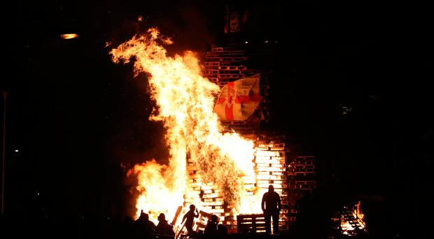 Crowds watch as a bonfire is lit in the New Lodge area of Belfast to mark the anniversary of the introduction of the controversial policy of internment without trial. (PA)