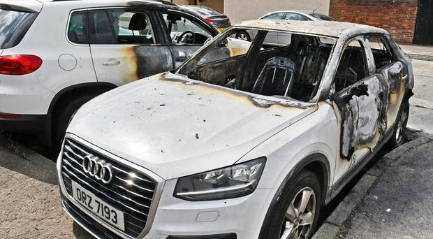 Two of the vehicles that were burnt out at Carlisle Terrace in the New Lodge Road area of North Belfast overnight. Credit: Alan Lewis/Photopress