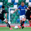 Linfield's Andrew Mitchell (centre) and Qarabag's Jamie Romero (right) battle for the ball during the UEFA Europa League play-off first leg match at Windsor Park, Belfast. PRESS ASSOCIATION Photo. Picture date: Thursday August 22, 2019. See PA story SOCCER Linfield. Photo credit should read: Niall Carson/PA Wire