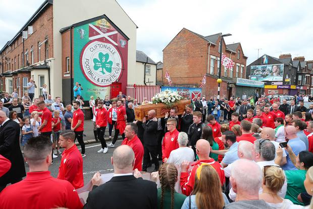Tommy Breslin's coffin, flanked by Cliftonville player past and present along with managers, travels along the Cliftonville Road near to Cliftonville's ground Solitude. Credit: Jonathan Porter/PressEye