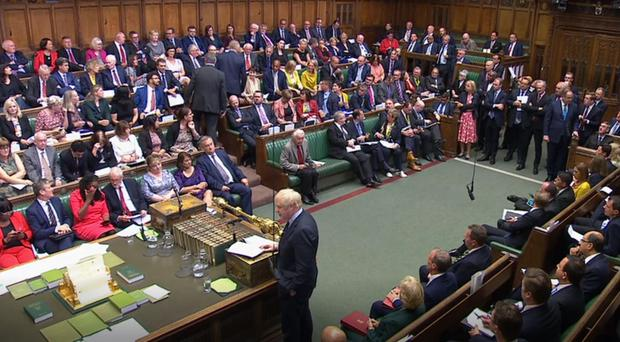 Phillip Lee (centre standing right) takes his seat among Liberal Democrat MPs as Prime Minister Boris Johnson makes a statement to MPs (House of Commons/PA)