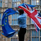 A man waves both a Union flag and a European Union flag on College Green, Westminster