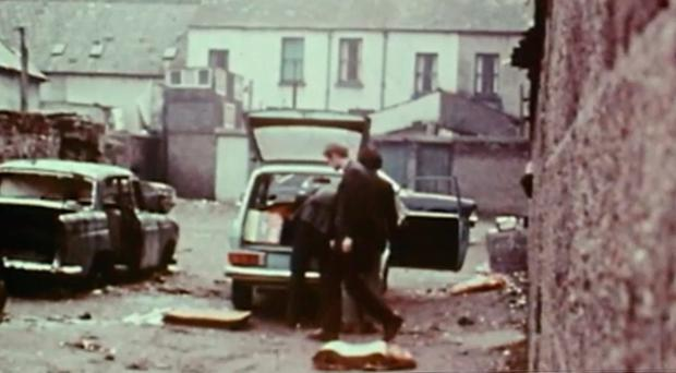 Martin McGuinness walking behind a bomb being placed in a car in Derry in 1972. Footage from BBC Spotlight