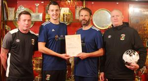 Glentoran Disability FC coach Jordan Wray receives the UEFA silver grassroots award certificate from the Irish FA Foundation's Alan Crooks as Mark Smith and Stephen Lowry look on.
