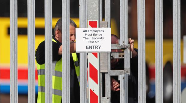 Security workers close the gates at the Wrightbus plant in Ballymena (Liam McBurney/PA)