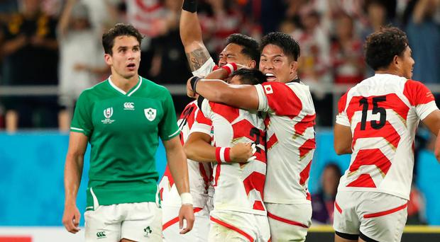 Joey Carbery (l) looks on as the Japan team celebrate victory.