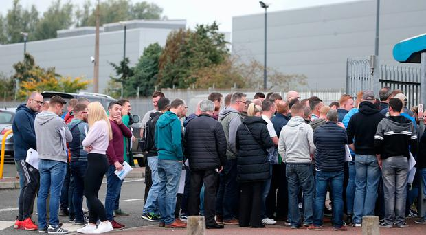 Workers queue outside one of the firm's factories for help with gaining further employment