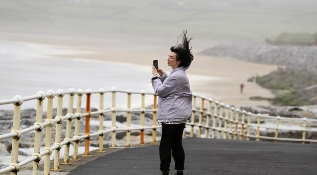 People walk along the sea front in Lahinch, County Clare, as storm Lorenzo makes landfall (Brian Lawless/PA)
