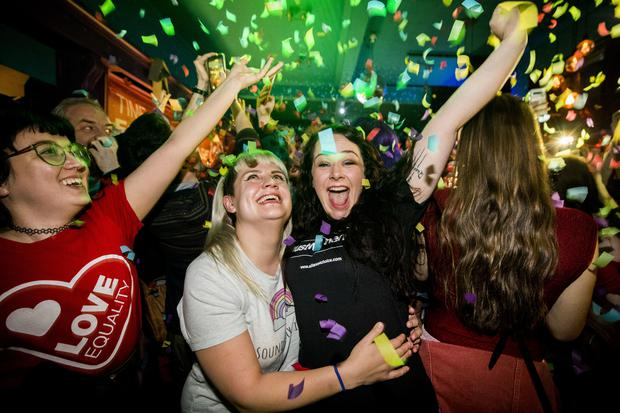 Martha Brown (left, grey t-shirt) with her partner Louise McCullough (right, black t-shirt) and equal marriage supporters at Maverick Bar, Belfast, celebrate the change to abortion and same sex marriage laws in Northern Ireland (Liam McBurney/PA)
