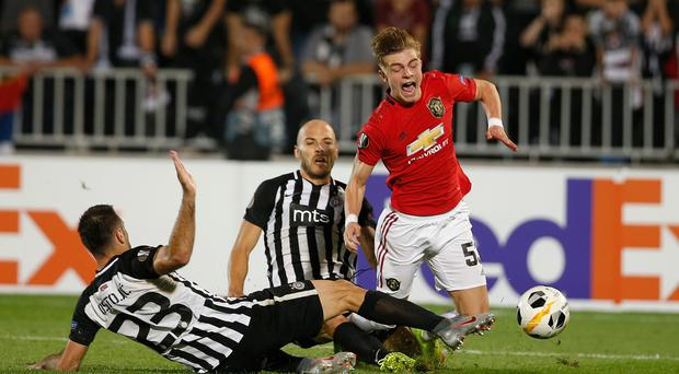 Manchester United's Brandon Williams, right, is fouled by Partizan's Bojan Ostojic, left, and Zoran Tosic, 2nd left, during their Europa League group L soccer match at the Partizan stadium in Belgrade, Serbia, Thursday, Oct. 24, 2019. (AP Photo/Marko Drobnjakovic)