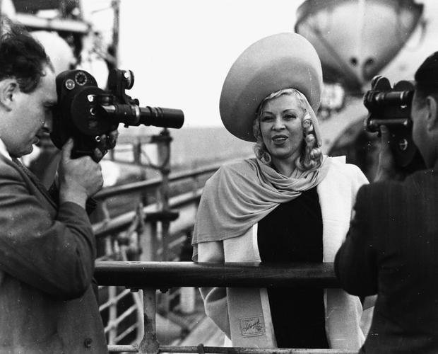 Sailing in: Mae West is interviewed on the deck of the Queen Mary ship on its arrival at Southampton in 1947