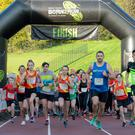 Runners cross the finish line at the Belfast Telegraph Run Forest Run event at Minnowburn, Belfast. Credit: Mervyn McKeown/My Sports Photo