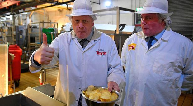 Prime Minister Boris Johnson with Tayto Chairman Stephen Hutchinson. (Photo by Daniel LEAL-OLIVAS / POOL / AFP) (Photo by DANIEL LEAL-OLIVAS/POOL/AFP via Getty Images)