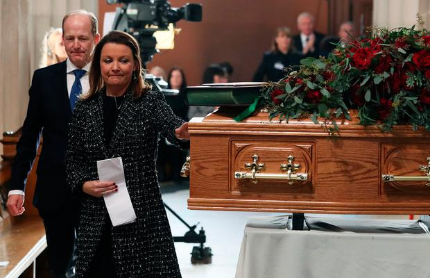 Suzy O'Byrne, daughter of the celebrated broadcaster Gay Byrne, touches her fathers coffin during his funeral service in St. Mary's Pro-Cathedral in Dublin.