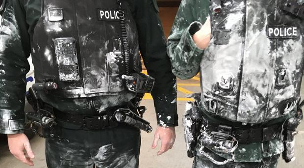 Police officers in the Lisburn area who had paint thrown over them as the chased a suspect who cut off his ankle tag. Credit: PSNI