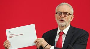 Labour Party leader Jeremy Corbyn holds up a leaked document relating to Northern Ireland (Jonathan Brady/PA)