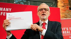 Labour Party leader Jeremy Corbyn holds up a leaked document relating to Northern Ireland, during a press conference in central London. Jonathan Brady/PA Wire