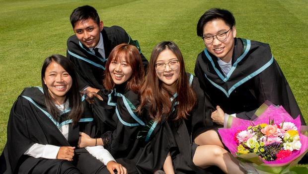 A group of students from Malaysia and China celebrate as they graduate from Queen's University Belfast today with a degree in Architecture.