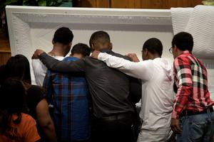 TOPSHOTS Mourners pay their respects at the casket of Freddie Gray before his funeral at New Shiloh Baptist Church April 27, 2015 in Baltimore, Maryland. Family members and friends are expected to turn out in large numbers Monday at the funeral of Gray, the 25-year-old black man who died April 19 after an encounter April 12 with police left him with grave spinal injuries.  PHOTO/BRENDAN SMIALOWSKIBRENDAN SMIALOWSKI/AFP/Getty Images