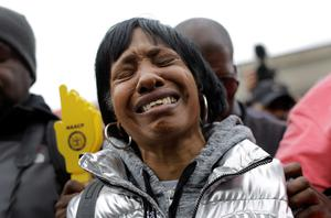 Angela Hazel reacts during a moment of silence before a protest march for Freddie Gray, Thursday, April 23, 2015, in Baltimore. Gray died from spinal trauma a week after being arrested by a group of officers, hoisted into police van and driven to a Baltimore station. (AP Photo/Patrick Semansky)
