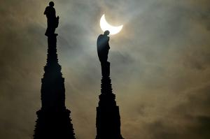 A partial solar eclipse of the sun is visible next to the statues of Milan's cathedral on March 20, 2015.  AFP/Getty Images