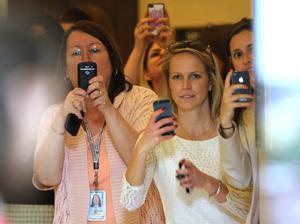 WASHINGTON, DC - MAY 09:  Women watch and take camera phone pictures as HRH Prince Harry tours an anti-landmine photography exhibition by The HALO Trust charity during the first day of his visit to the United States at the Russell Senate Office Building on May 9, 2013 in Washington, DC. HRH will be undertaking engagements on behalf of charities with which the Prince is closely associated on behalf also of HM Government, with a central theme of supporting injured service personnel from the UK and US forces.  (Photo by Chris Jackson-Pool/Getty Images)